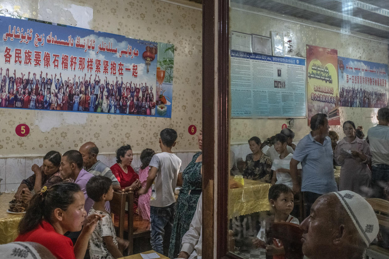 "Patrons dine under posters quoting Xi Jinping, reading ""every ethnic group must tightly bind together like the seeds of a pomegranate,"" at a restaurant in Yarkand, in China's Xinjiang province, Aug. 5, 2019. (Gilles Sabrié/The New York Times)"
