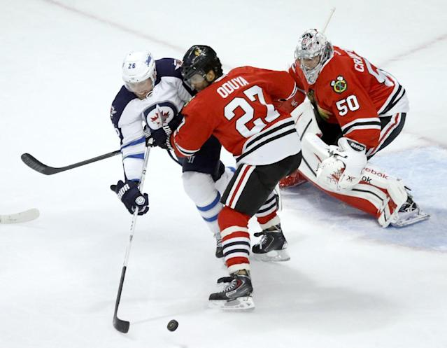 Chicago Blackhawks defenseman Johnny Oduya (27) keeps Winnipeg Jets right wing Blake Wheeler (26) away from a loose puck as goalie Corey Crawford defends during the first period of an NHL hockey game, Sunday, Jan. 26, 2014, in Chicago. (AP Photo/Charles Rex Arbogast)
