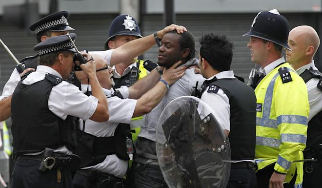British police officers arrest a man after riots spread through London in August 2011. Photo: AP