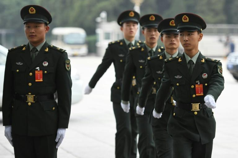 Chinese soldiers march outside the Great Hall of the People on the eve of the opening of the 19th Communist Party Congress