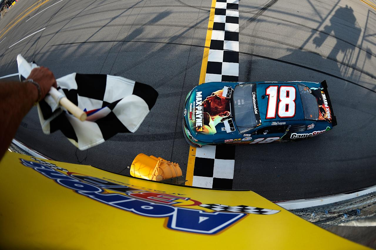 TALLADEGA, AL - MAY 05:  Joey Logano, driver of the #18 GameStop Toyota, celebrates with the checkered flag after winning the NASCAR Nationwide Series Aaron's 312 at Talladega Superspeedway on May 5, 2012 in Talladega, Alabama.  (Photo by Jared C. Tilton/Getty Images)