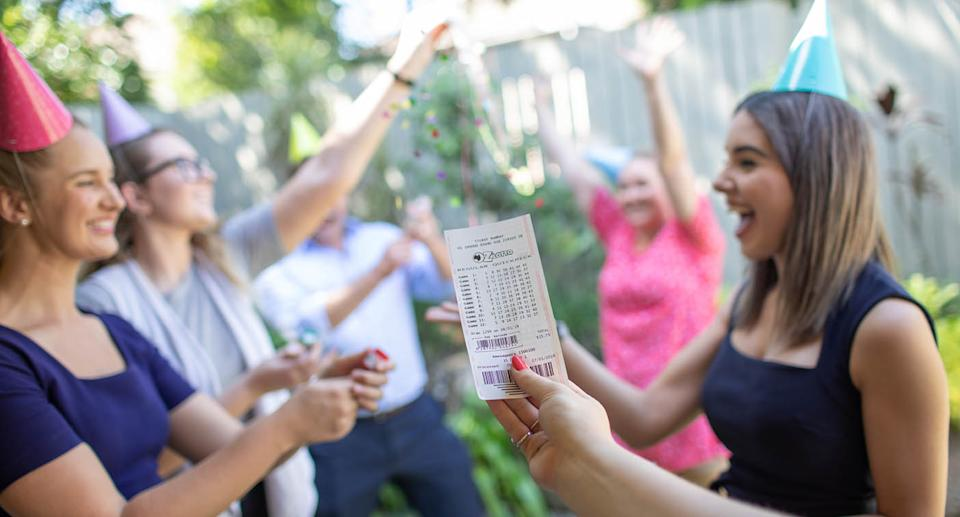 Woman holds up winning tickets as people celebrate. Source: The Lott