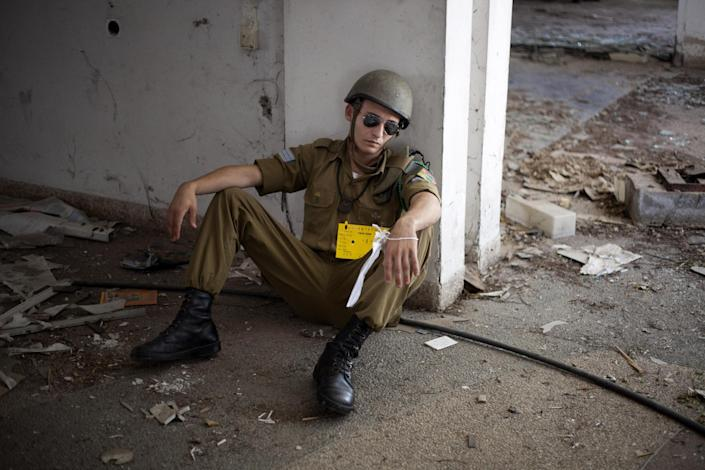 An Israeli soldier acting as if he is wounded waits for Israeli soldiers of the Home Front Command rescue unit during a drill in Azur, near Tel Aviv, Israel, Tuesday, May 28, 2013. Israel has launched a national civil defense drill, which the army said this year will focus on the threat of unconventional weapons at a time of growing regional tensions. (AP Photo/Ariel Schalit)
