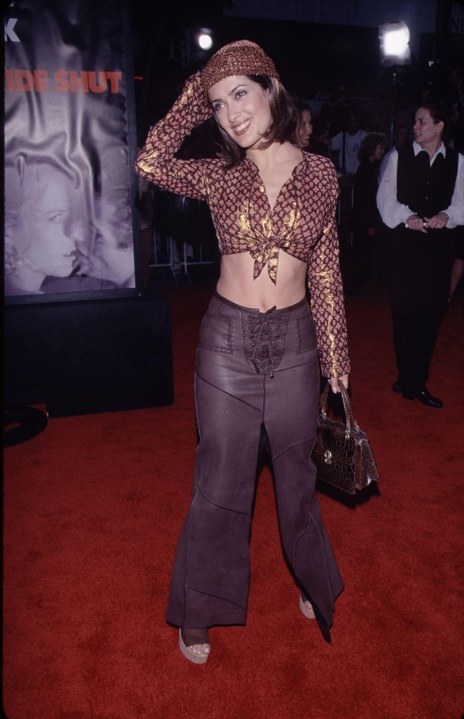 <p>At the <em>Eyes Wide Shut</em> premiere, Salma went with a button-down tied into a crop top, a crochet beanie, and a high-waisted leather skirt with lace-up details. </p>