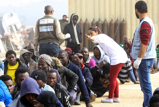 <p>Workers from the office of the United Nations High Commissioner for Refugees (UNHCR) tend to African migrants rescued from a ship off the coast of Zawiyah, about 45 kilometres west of the Libyan capital Tripoli, as they sit at the dock at the capital's naval base on March 10, 2018. (Photo: Mahmud Turkia/AFP/Getty Images) </p>