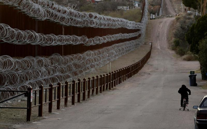A boy rides his bike along a razor-wire-covered border wall that separates Arizona from Mexico - AP