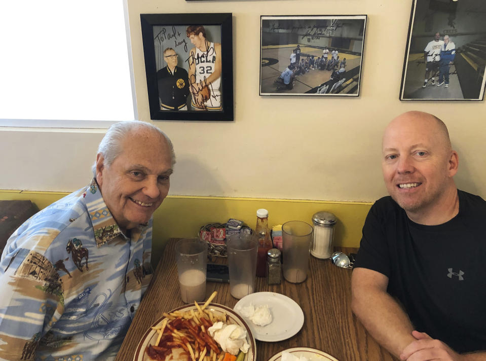 In this 2019 photo provided by UCLA Athletics, Hep Cronin, left, sits with his son UCLA men's basketball coach Mick Cronin, right, at the Wooden's booth at VIP's Cafe in the Tarzana section of Los Angeles where legendary UCLA coach John Wooden used to have breakfast every morning. Mike's dad has become an unlikely celebrity during the Bruins' run to the Final Four in his son's second season in Westwood. (UCLA Athletics via AP)