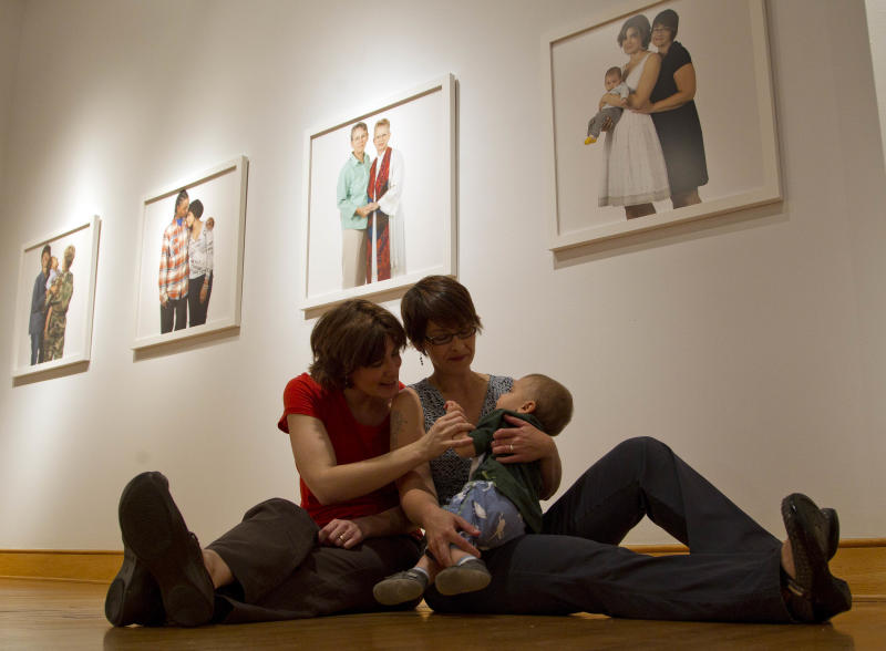 Hanne Harbison, left, and her partner Anna Koopman sit with their son Amon, 9 months, beneath their portrait, at right, Thursday, March 29, 2012 at the Civil Rights Institute in Birmingham, Ala. A show of photographs of lesbian families by Carolyn Sherer will be on display at the institute through June. (AP Photo/Dave Martin)
