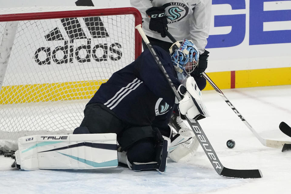 FILE - Seattle Kraken goalie Philipp Grubauer watches the puck as he takes part in a practice session during a media event for the grand opening of the Kraken's NHL hockey practice and community facility in Seattle, in this Thursday, Sept. 9, 2021, file photo. This was an unprecedented offseason of goaltender movement around the NHL. Vegas traded Vezina Trophy winner Marc-Andre Fleury to Chicago. Finalist Philipp Grubauer couldn't agree to a deal with Colorado and signed with expansion Seattle in free agency. And those moves set off a domino effect that included 25 different goalies changing teams. (AP Photo/Ted S. Warren, File)
