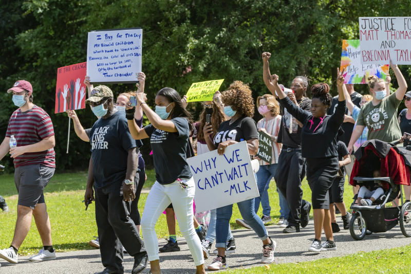 In a Saturday, June 6, 2020 photo, people walk in Gould Park in Vidor, Texas. Several hundred people came out to the park on Saturday afternoon for a protest and peace march in honor of George Floyd who died while being detained by Minneapolis police. (Fran Ruchalski/The Beaumont Enterprise via AP)