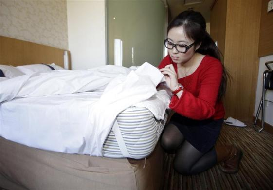 Ms. Zhuang, a Hotel Test Sleeper, checks the bed of a business chain hotel in Beijing March 6, 2012.