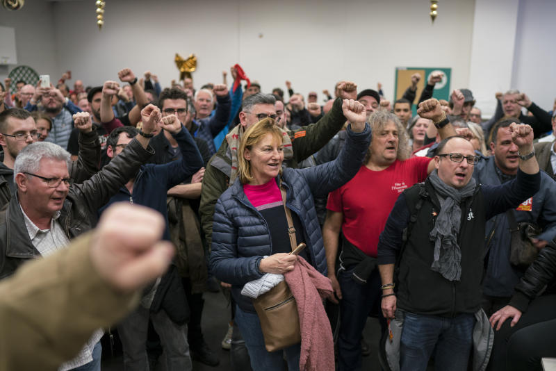 Striking dock workers gesture, during a union assembly at the Marseille port in southern France, Thursday, Jan. 23, 2020. Protesters marched in Paris against French President Emmanuel Macron's plans to overhaul the pension system. (AP Photo/Daniel Cole)