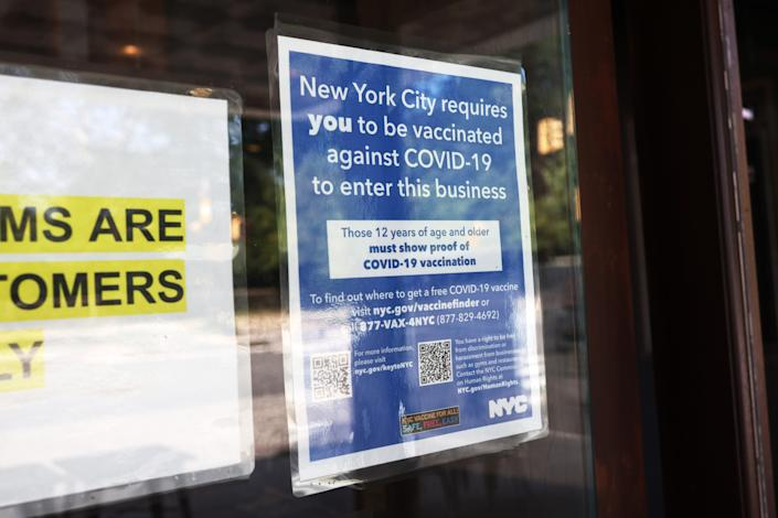 A sign warning that theatergoers must be vaccinated is posted at the entrance of Nighthawk Cinema on Wednesday in Brooklyn, N.Y.