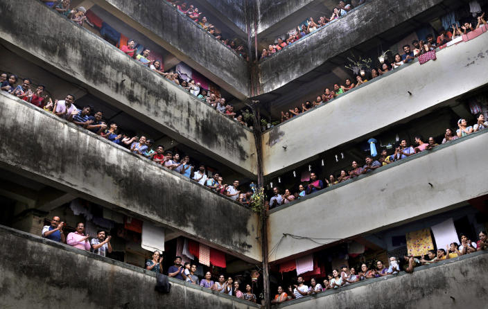 People clap from balconies in a show of appreciation for health care workers in Mumbai, India, Sunday, March 22, 2020. (AP Photo/Rafiq Maqbool)