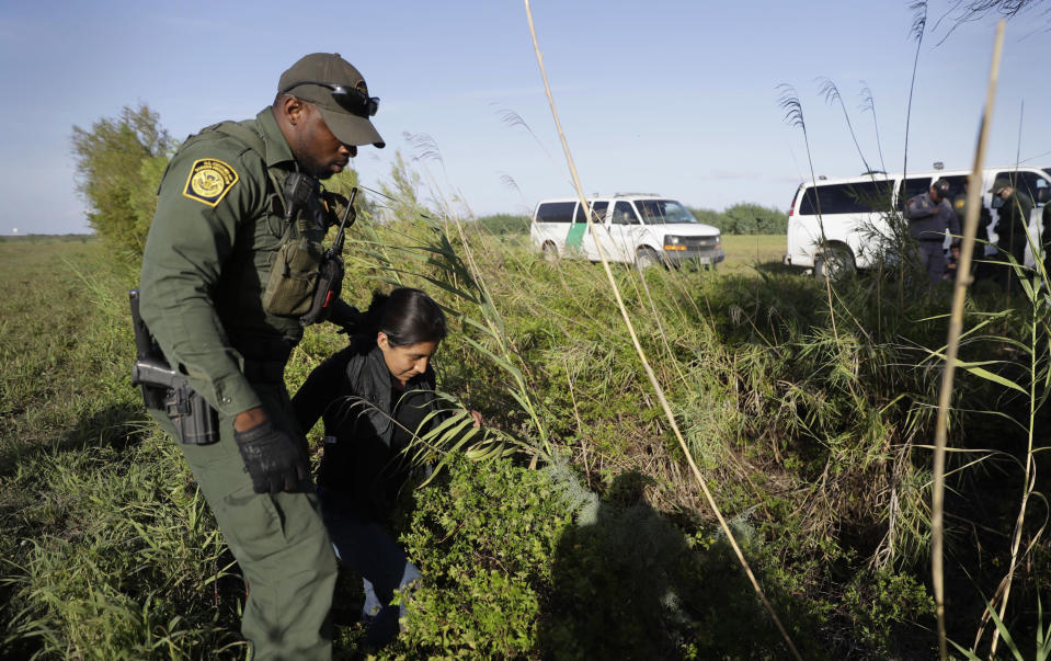 FILE - In this Aug. 11, 2017 file photo a U.S. Customs and Border Patrol agent escorts an immigrant suspected of crossing into the United States illegally along the Rio Grande near Granjeno, Texas. The number of unaccompanied children encountered on the U.S. border with Mexico in April 2021 eased from an all-time high a month earlier, while more adults are coming without families. Authorities encountered nearly 17,200 children traveling alone, down 9% from March but still far above the previous high in May 2019. (AP Photo/Eric Gay, File)