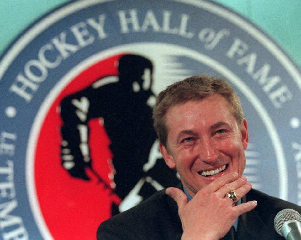 FILE - Hockey legend Wayne Gretzky laughs as he wears his new Hockey Hall of Fame ring during his induction ceremony at the Hall in Toronto, in this Monday Nov. 22, 1999, file photo. Alex Ovechkin starts a new five-year contract ready to chase Wayne Gretzky's career goals record that long seemed unbreakable. The Washington Capitals captain has 730 goals and needs 165 to pass Gretzky. (AP Photo/Frank Gunn, File)