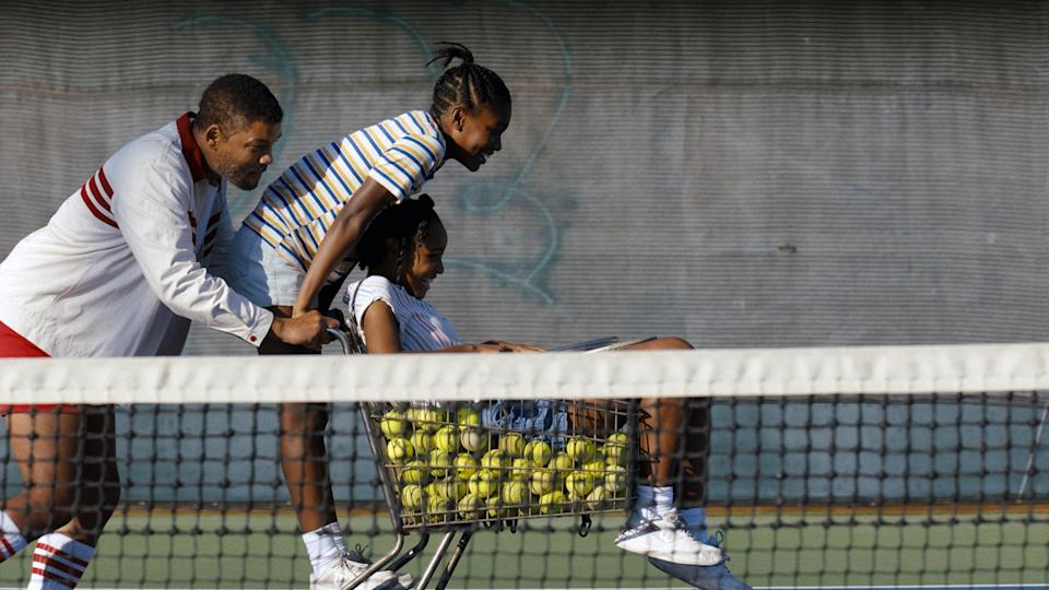 Richard pushing Venus and Serena across a tennis court as they ride on a shopping cart filled with tennis balls