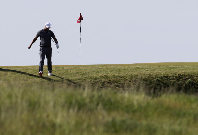 Brooks Koepka walks down to his ball in a bunker on the 11th hole during the final round of the U.S. Open Golf Championship, Sunday, June 17, 2018, in Southampton, N.Y. (AP Photo/Julio Cortez)