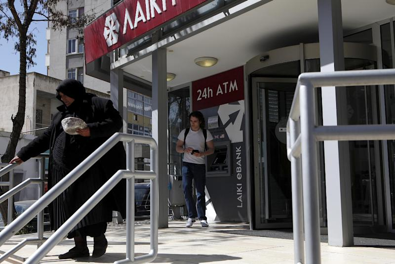 """An elderly woman leaves the Bank as another man leaves the ATM machine in central capital Nicosia, Cyprus, Wednesday, March 13, 2013. Cyprus' president Nicos Anastasiades says talks with international creditors for a much-needed rescue loan to keep the country from going bankrupt are paying off. Anastasiades urged patience, saying that it will soon become clear that """"hard work produces good results."""" (AP Photo/Petros Karadjias)"""