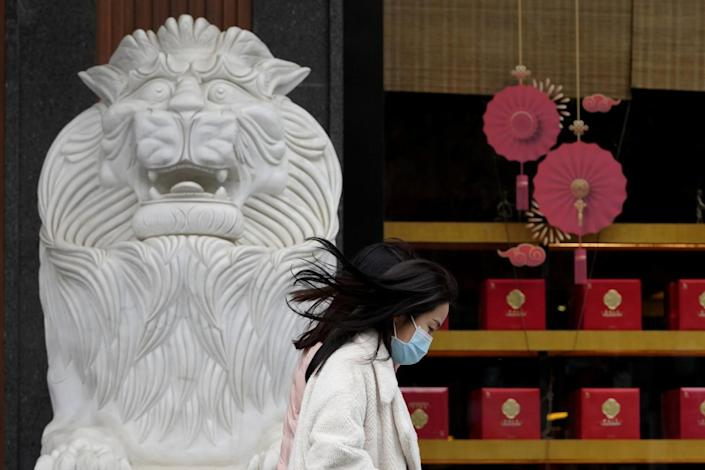 A woman walks past a stone lion and Lunar New Year decorations.
