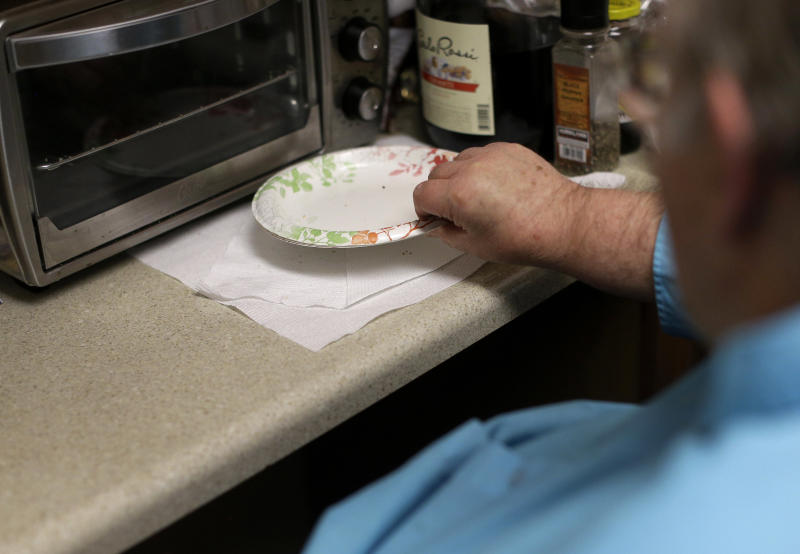 In this Dec. 21, 2013 photo, George Warren, a resident at Village Crossroads, an affordable senior community in Nottingham, Md., tidies up his kitchen. Warren, 63, reuses paper towels to stretch his fixed-income budget. (AP Photo/Patrick Semansky)