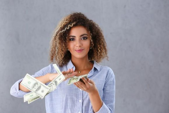 a young woman makes it rain by flinging dollar bills at camera.