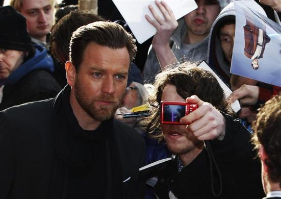 "Actor Ewan McGregor has a photograph taken with a fan as he arrives for the European premiere of ""Salmon Fishing in the Yemen"" in London, April 10, 2012."