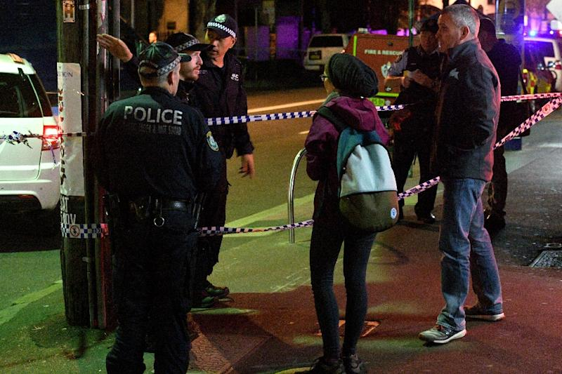 Police speak to passersby as they man a check point in the inner Sydney suburb of Surry Hills on July 29, 2017. Four people were arrested in a series of raids across Sydney on July 29 (AFP Photo/William WEST)
