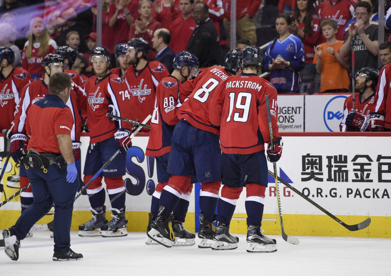 Washington Capitals left wing Alex Ovechkin (8), of Russia, is helped off the ice by Nicklas Backstrom (19), of Sweden, and Nate Schmidt (88) after he was injured during the first period of Game 5 in an NHL Stanley Cup hockey first-round playoff series against the Toronto Maple Leafs, Friday, April 21, 2017, in Washington. (AP Photo/Nick Wass)