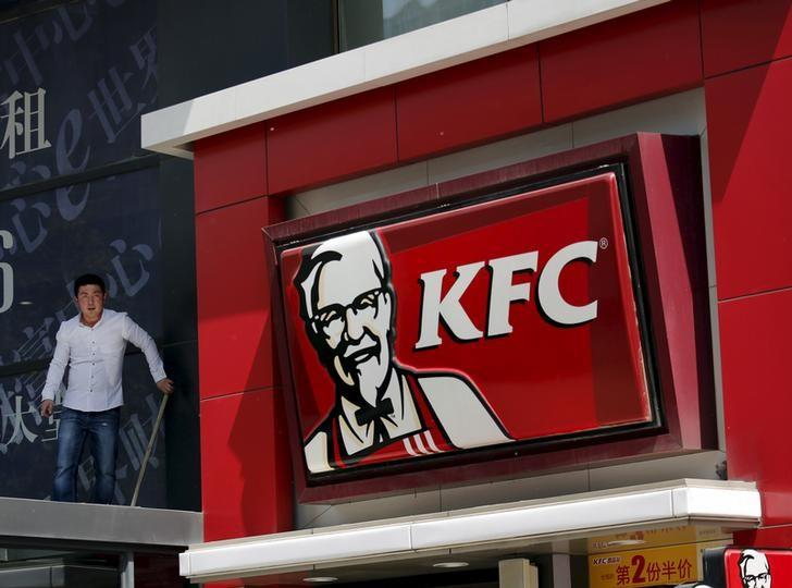 Worker cleans an exterior of a building next to a KFC restaurant in Beijing
