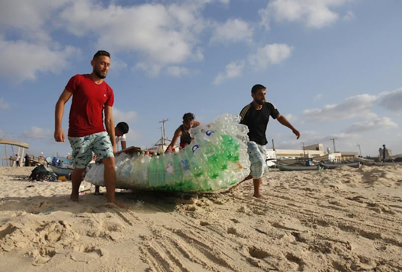 Palestinian fisherman Mouad Abu Zeid (R) and his friends carry his boat, made of 700 plastic bottles, into the sea off Rafah in the southern Gaza Strip on August 14, 2018 (AFP Photo/SAID KHATIB)
