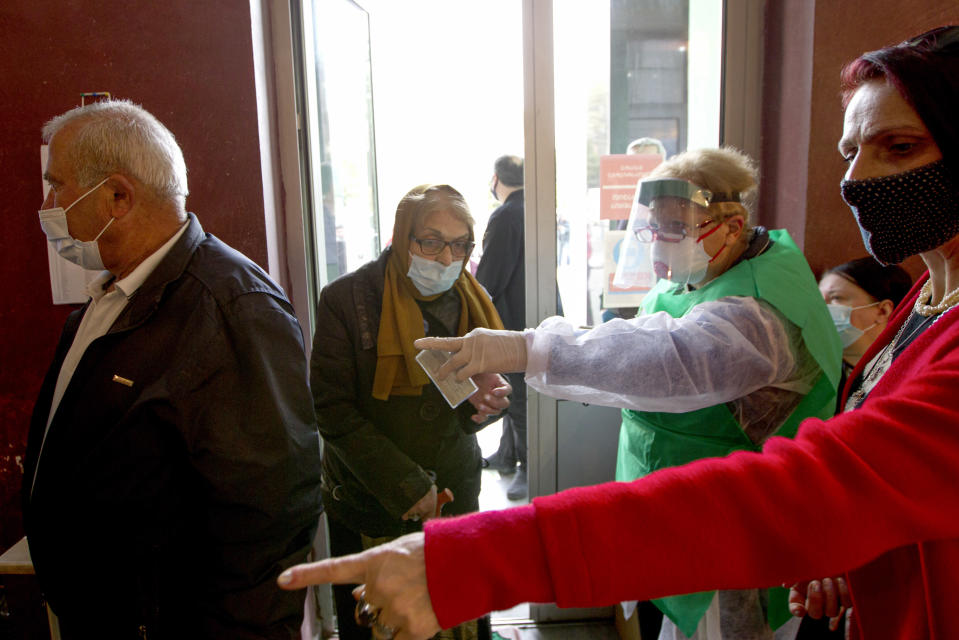 A woman wearing a face mask to help curb the spread of the coronavirus, enter a polling station to vote during the parliamentary elections in Tbilisi, Georgia, Saturday, Oct. 31, 2020. The hotly contested election between the Georgian Dream party, created by billionaire Bidzina Ivanishvili who made his fortune in Russia and has held a strong majority in parliament for eight years, and an alliance around the country's ex-President Mikheil Saakashvili, who is in self-imposed exile in Ukraine. (AP Photo/Shakh Aivazov)