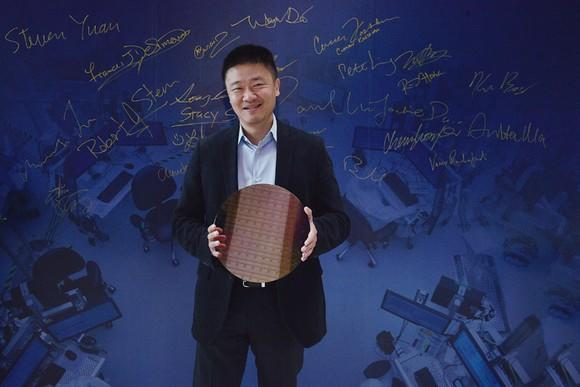 An executive from Arm holding a test wafer of Intel 10-nanometer chips.