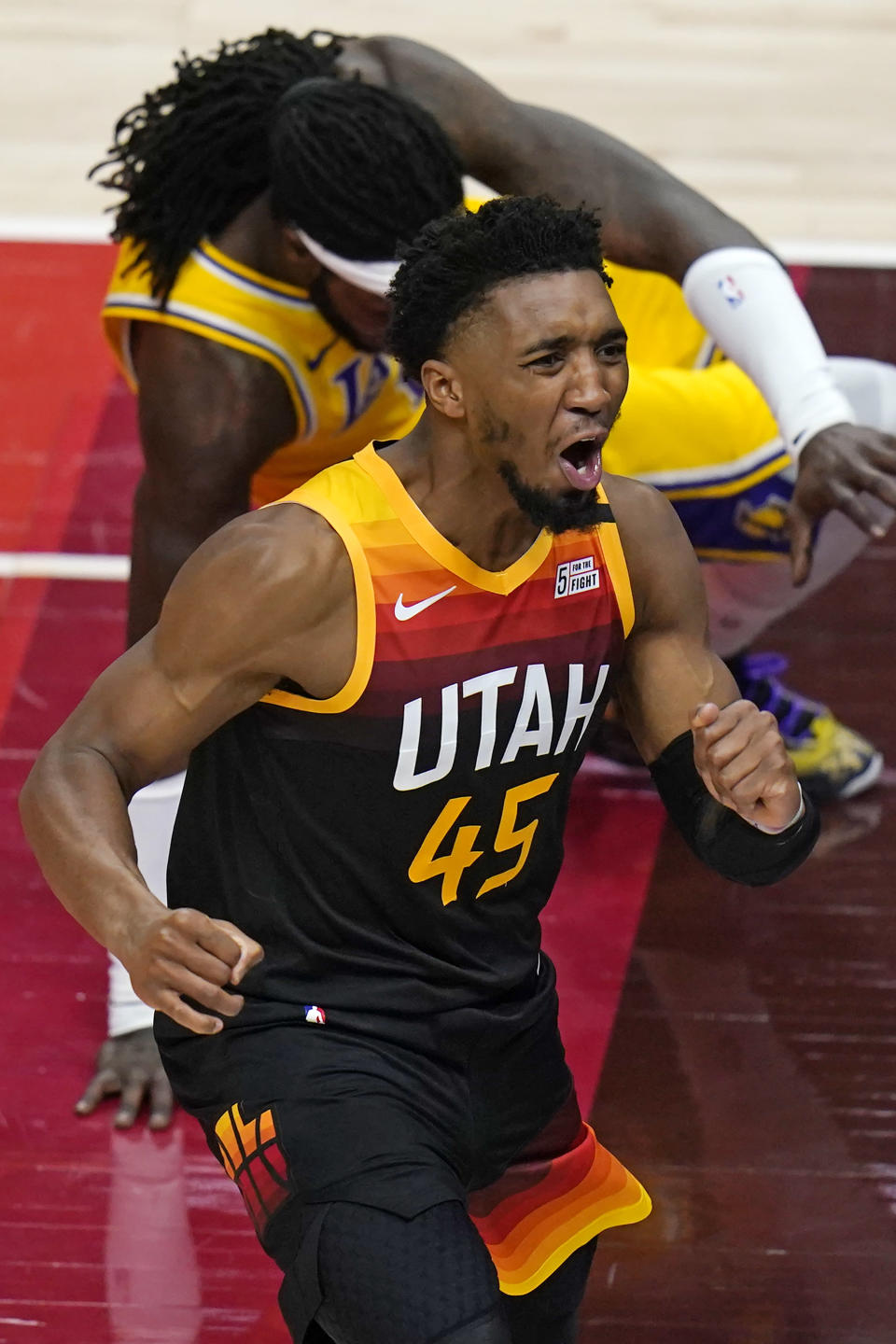 Utah Jazz guard Donovan Mitchell (45) reacts after blocking a shot by Los Angeles Lakers center Montrezl Harrell, rear, during the first half of an NBA basketball game Wednesday, Feb. 24, 2021, in Salt Lake City. (AP Photo/Rick Bowmer)