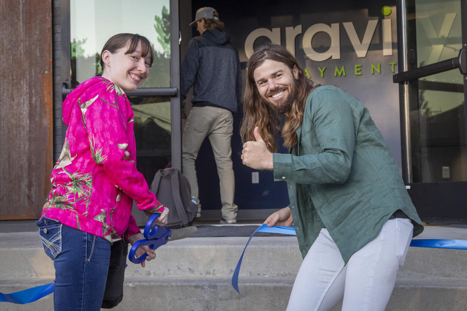 Dan Price, CEO and founder of Gravity Payments, recreates a ribbon-cutting with Rachel Redding, a QA analyst, for social media. (Katherine Jones/Idaho Statesman/Tribune News Service via Getty Images)