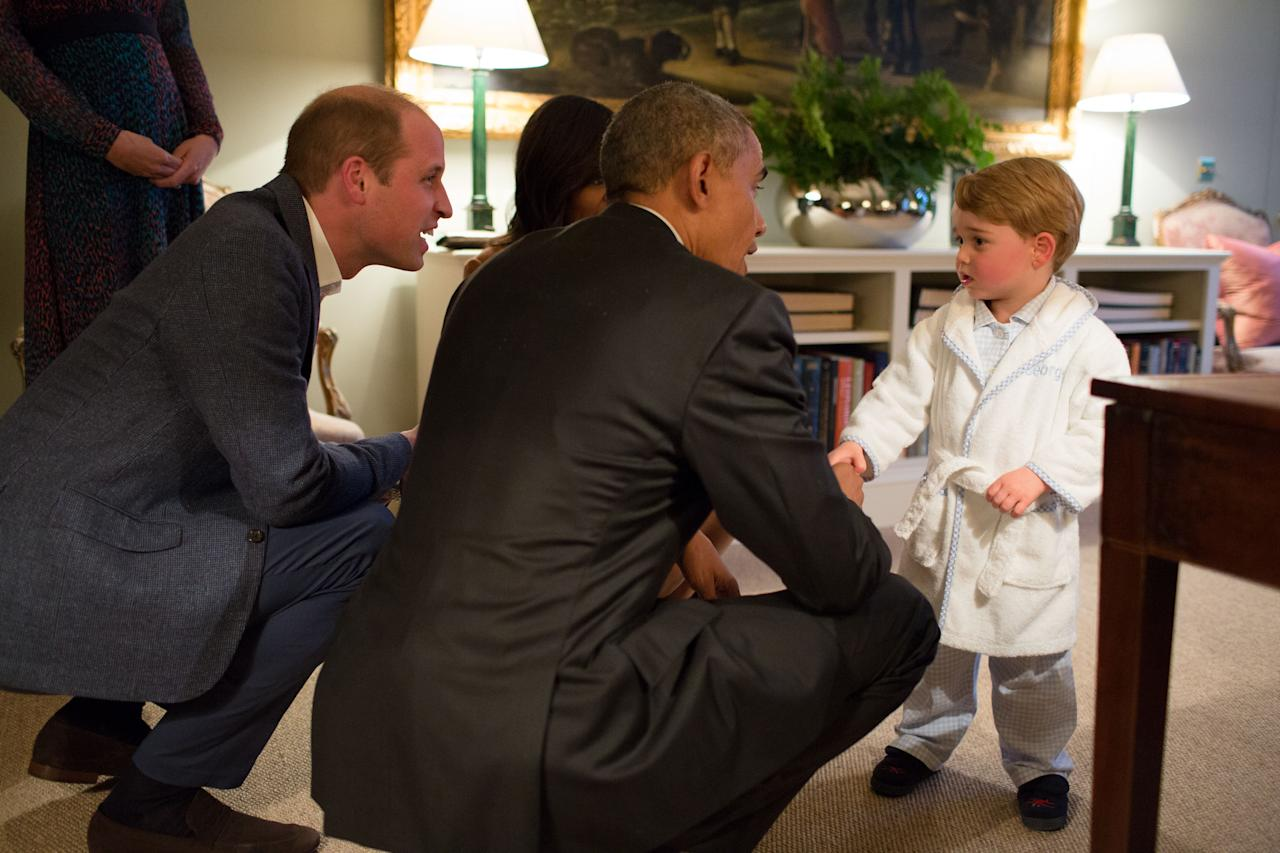 In this hand out photo released by Kensington Palace, Britain's Prince George meets with US President Barack Obama, centre and first lady Michelle Obama , at Kensington Palace, London, Friday April 22, 2016. Prince William is at left. (Pete Souza/Kensington Palace via AP)
