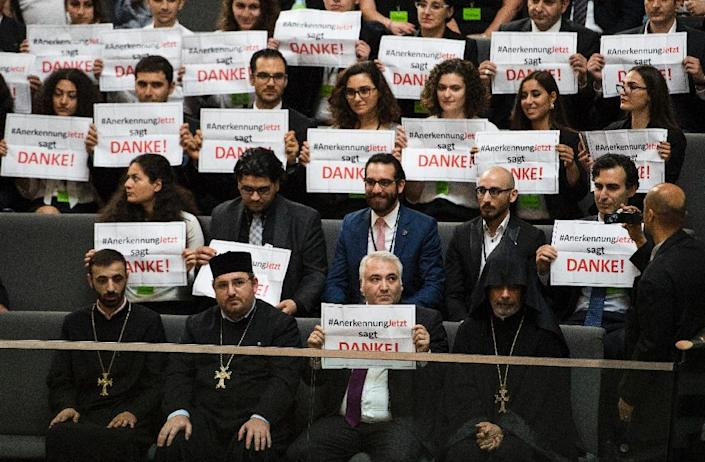 """Armenian clergy members and activists hold up banners saying """"thank you"""" in the Bundestag in Berlin after German lawmakers voted to recognise the Armenian genocide (AFP Photo/Odd Andersen)"""