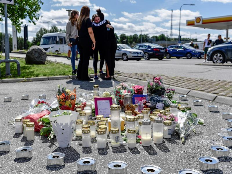 People stand near flowers and candles that have been left at the site where a 12-year-old girl was shot dead in Botkyrka, near Stockholm, Sweden: Stina Stjernkvist/TT News Agency via REUTERS