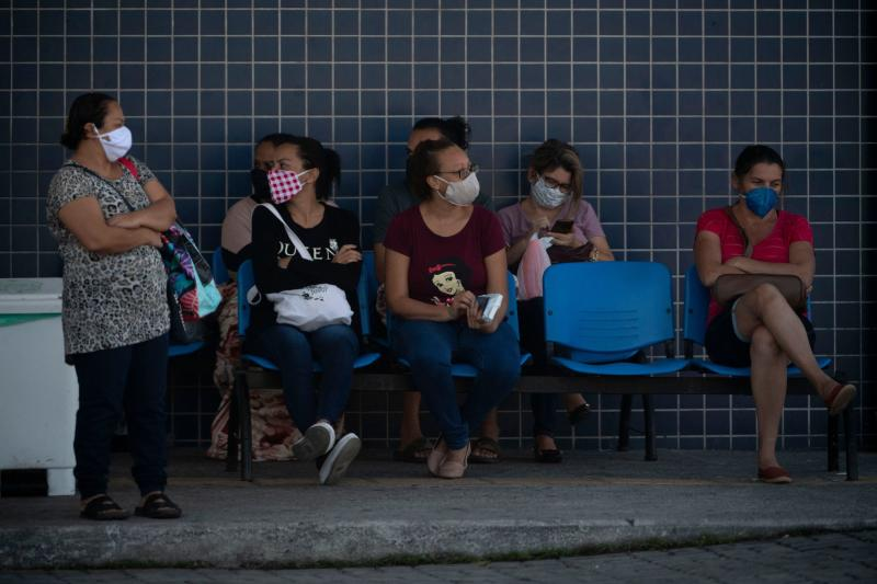 Women wait for care outside Evandro Freire Public Hospital during the novel coronavirus COVID-19 outbreak in Rio de Janeiro, Brazil, on April 29, 2020. - Brazil, the South American country worst-hit by the coronavirus pandemic, has registered more than 5,000 deaths from COVID-19, the health ministry announced Tuesday, pushing the toll above that of China. (Photo by MAURO PIMENTEL / AFP) (Photo by MAURO PIMENTEL/AFP via Getty Images)