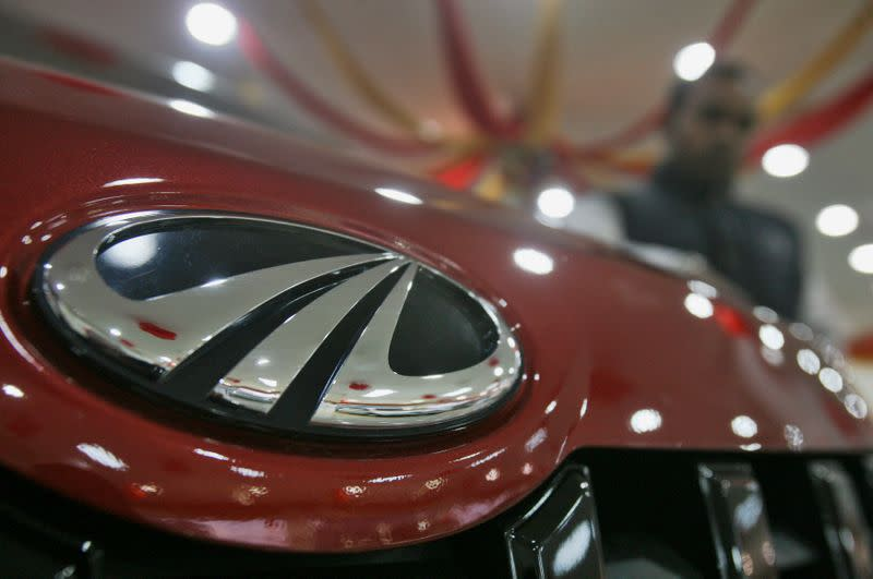 A customer stands next to a Mahindra vehicle on display inside the company's showroom in Chandigarh