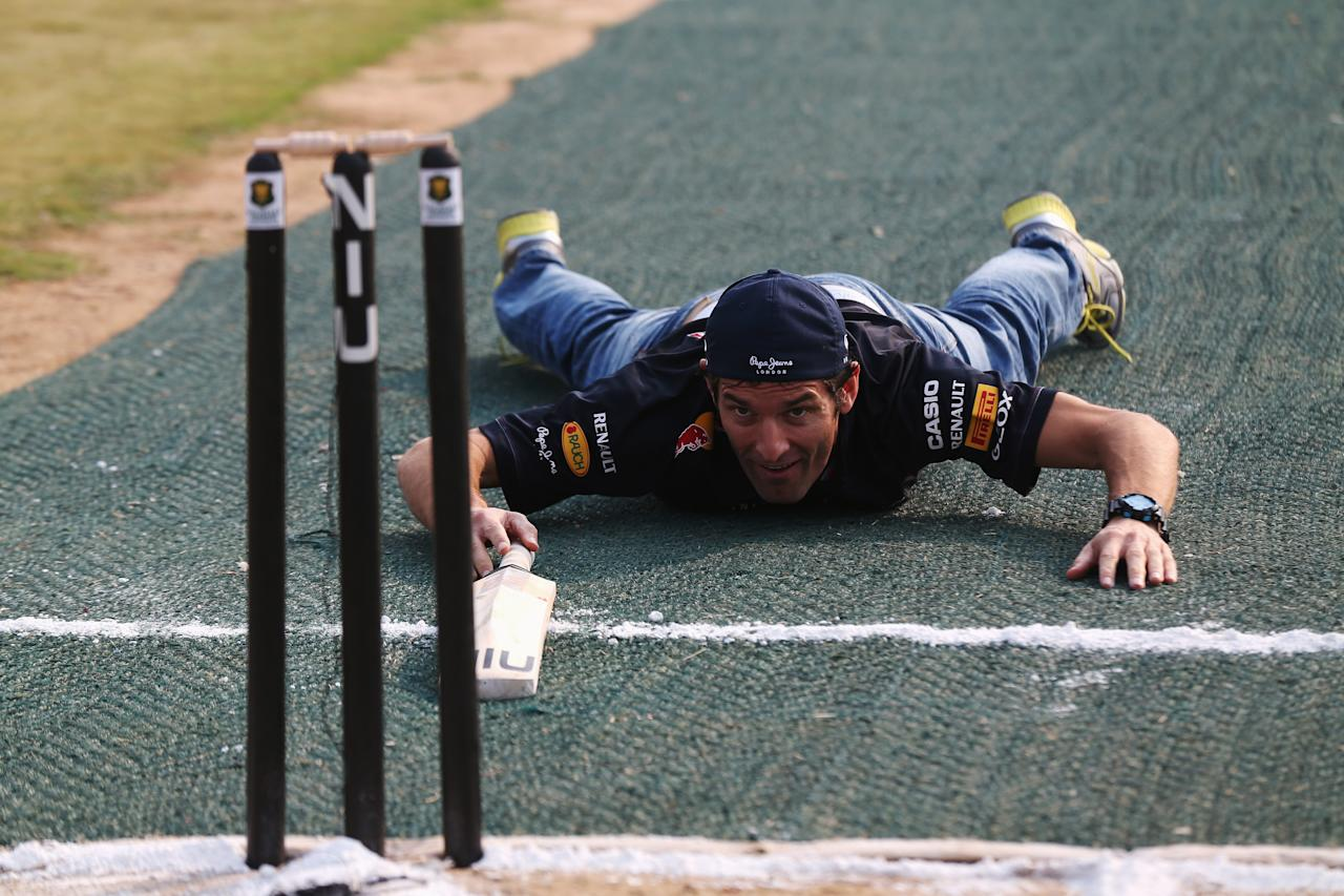 NOIDA, INDIA - OCTOBER 24:  Mark Webber of Australia and Red Bull Racing tries his hand at batting with Indian cricketer Gautam Gambhir (unseen) during previews for the Indian Formula One Grand Prix on October 24, 2012 in Noida, India.  (Photo by Mark Thompson/Getty Images)