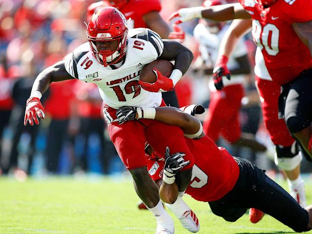 <p>Louisville running back Hassan Hall (19) tries to break the tackle from Western Kentucky linebacker Malik Staples (9) during the first half of play in a game between the Cardinals and the Hilltopers on Sept. 14, 2019 in Nashville, Tennessee.</p>
