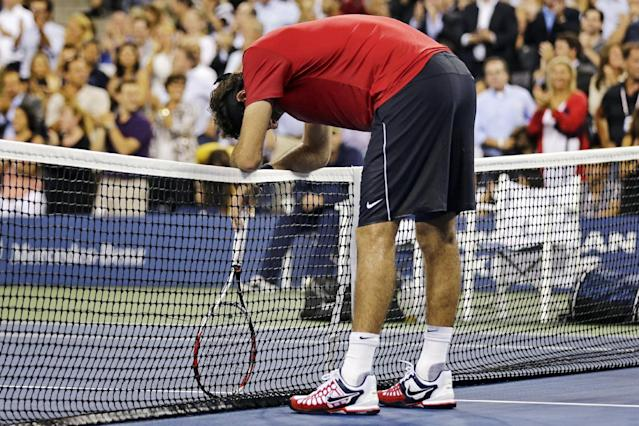 Juan Martin del Potro, of Argentina, rests on the net after losing a point during the second set against Novak Djokovic, of Serbia, in the quarterfinal round of play at the U.S. Open tennis tournament, Thursday, Sept. 6, 2012, in New York. (AP Photo/Charles Krupa)
