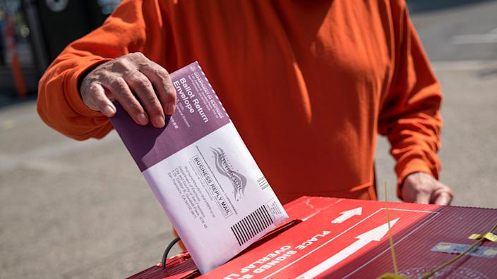 A resident drops a ballot inside a ballot box at an early voting polling location for the 2020 Presidential election in San Francisco, California, U.S., on Tuesday, Oct. 6, 2020. (David Paul Morris/Bloomberg via Getty Images)