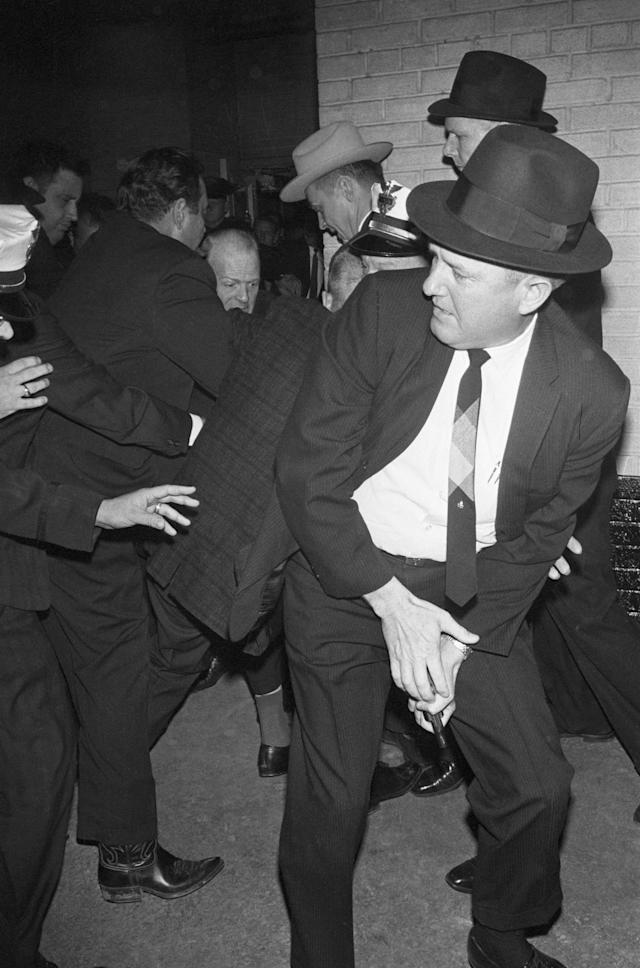 <p>Dallas police struggle with Jack Ruby, after the nightclub owner shoots the alleged assassin Lee Harvey Oswald in a corridor of Dallas police headquarters, Nov. 24, 1963. The officer in the foreground holds the gun Ruby used. (Photo: Bettmann/Getty Images) </p>