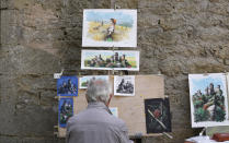A man paints drawings in downtown of San Marino, Sunday, Sept. 26, 2021. Tiny San Marino is one of the last countries in Europe which forbids abortion in any circumstance — a ban that dates from 1865. Its citizens are voting Sunday in a referendum calling for abortion to be made legal in the first 12 weeks of pregnancy. (AP Photo/Antonio Calanni)