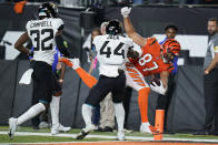 Cincinnati Bengals' C.J. Uzomah (87) goes in for a touchdown against Jacksonville Jaguars' Myles Jack (44) and Tyson Campbell (32) during the second half of an NFL football game, Thursday, Sept. 30, 2021, in Cincinnati. (AP Photo/Michael Conroy)