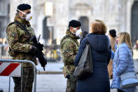 Italian soldiers wearing sanitary masks patrol Duomo square in downtown Milan, Italy, Monday, Feb. 24, 2020. At least 190 people in Italy's north have tested positive for the COVID-19 virus and four people have died, including an 84-year-old man who died overnight in Bergamo, the Lombardy regional government reported. (Claudio Furlan/Lapresse via AP)