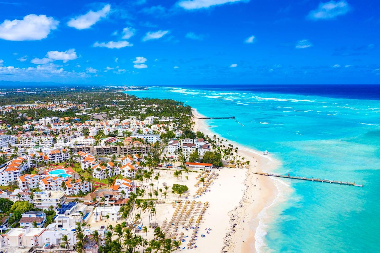 Aerial drone view of beautiful caribbean tropical beach with palms and straw umbrellas. Bavaro, Punta Cana, Dominican Republic. Vacation background