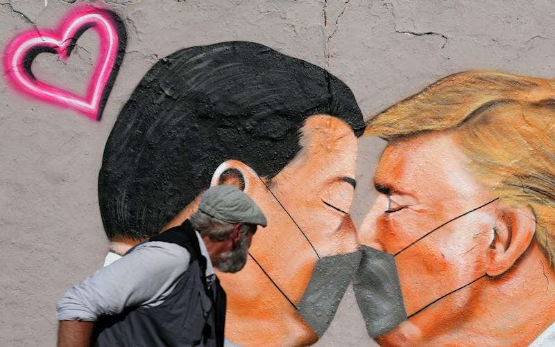 A pedestrian passes graffiti of Communist Party of China General Secretary Xi Jinping (L) and U.S. President Donald Trump kissing each other while wearing face masks during the coronavirus crisis on April 27, 2020 in Berlin